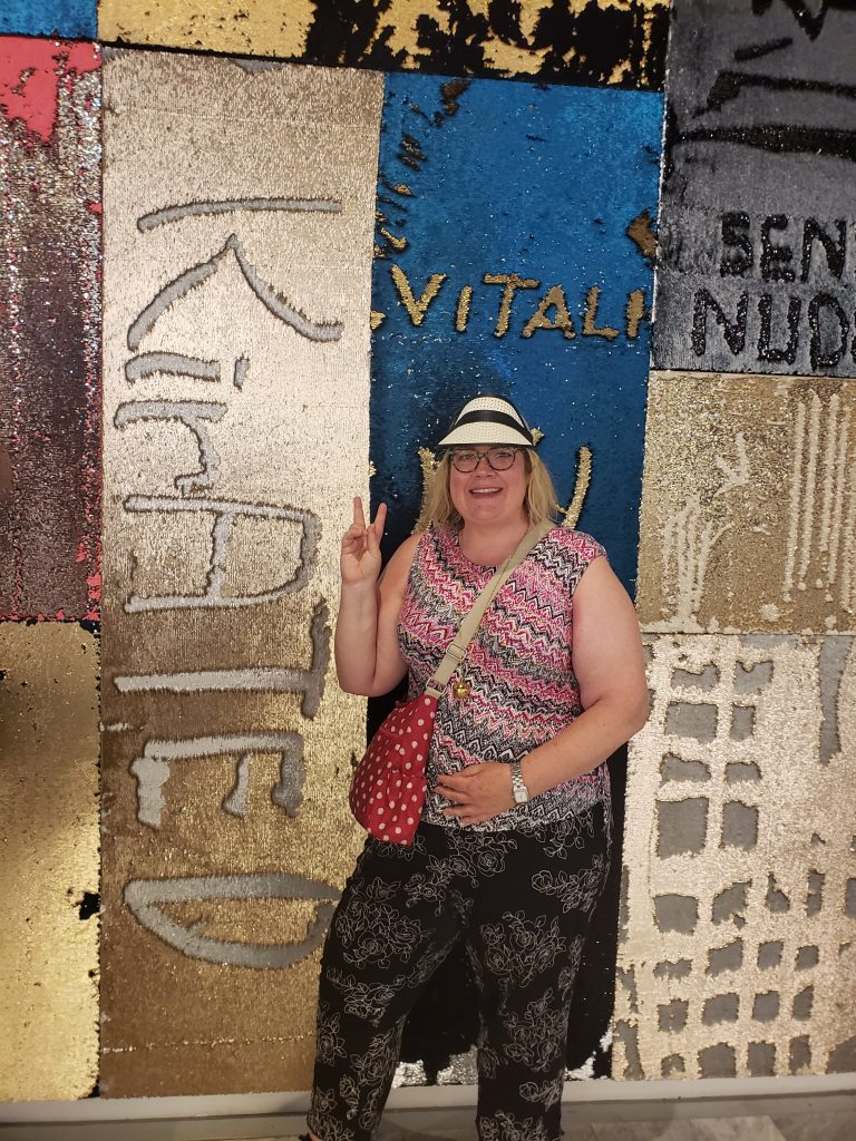 """Kirsten Voege of KIRated Communications at the sequin wall, aka """"I Was Here,"""" by Lara Schnitger at Hudson Yards in NYC"""